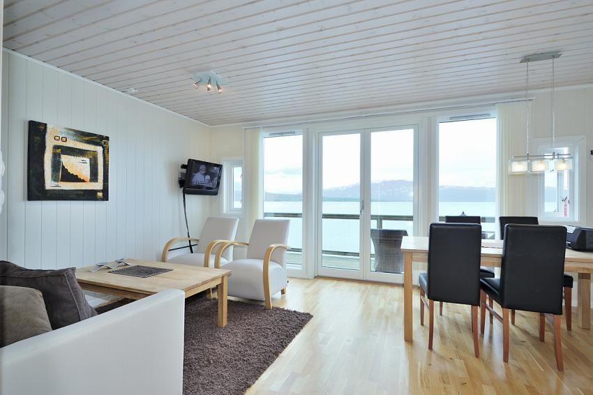 Romslig stue med parkett på gulv og rikelig med innslipp av lys fra store vindusflater
