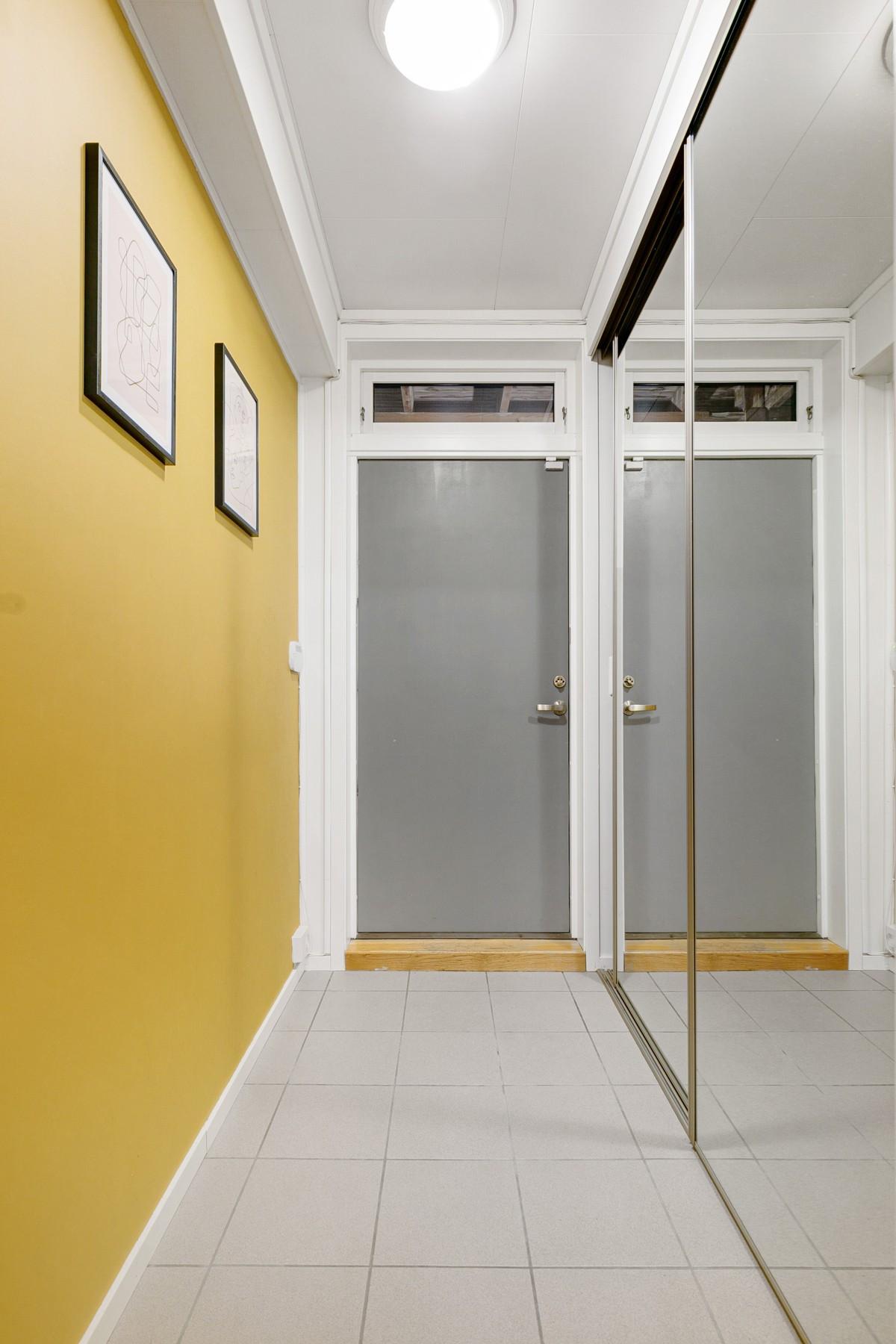 Vindfanget er flislagt med gulvvarme og har bred speilglassgarderobe med god plass til lagring