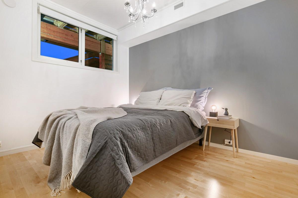 Soverommet er romslig med høye vinduer for lite innsyn, samt lun farge på vegg