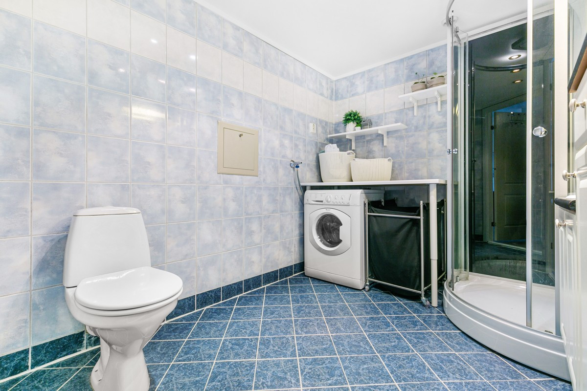Komplett fliselagt baderom med toalett, opplegg til vaskemaskin.
