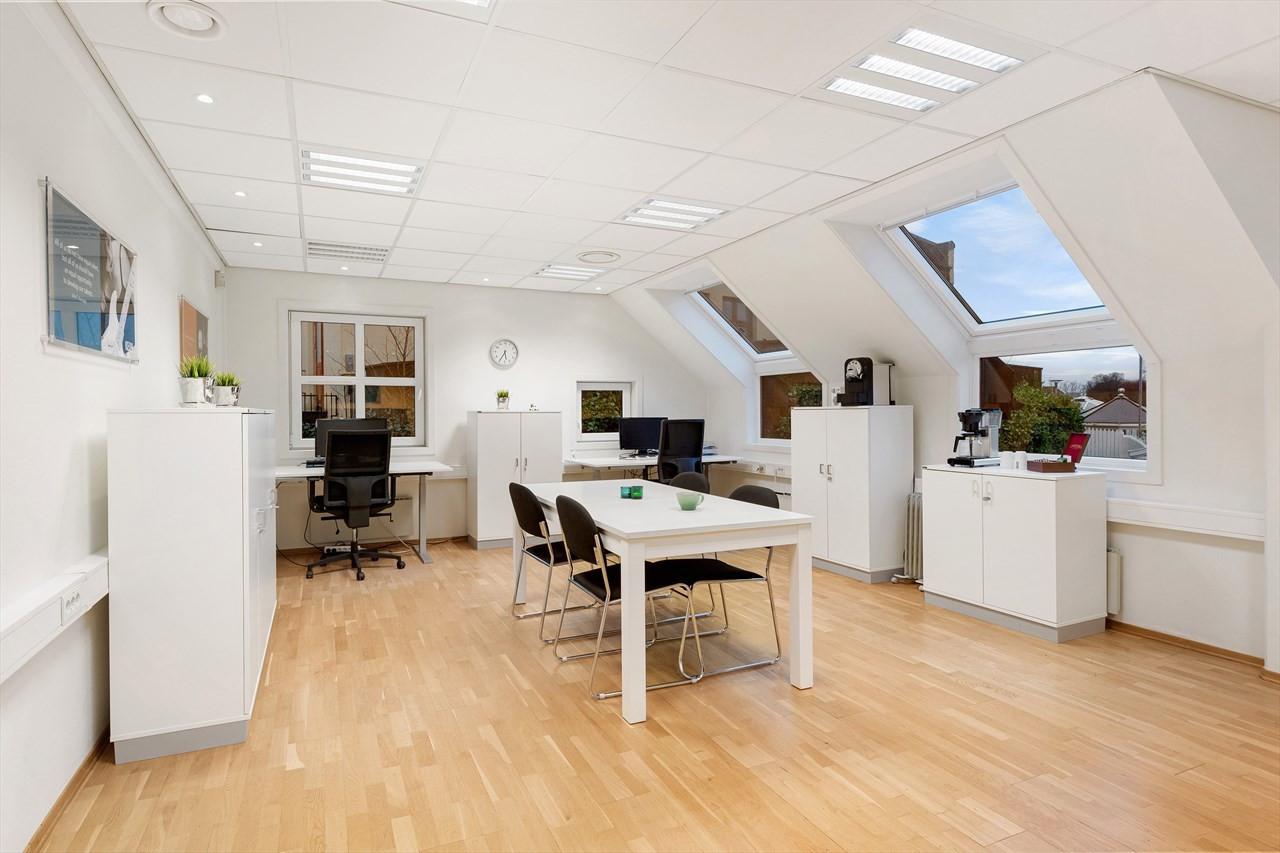 Romslig kontor med plass til flere arbeidsplasser.