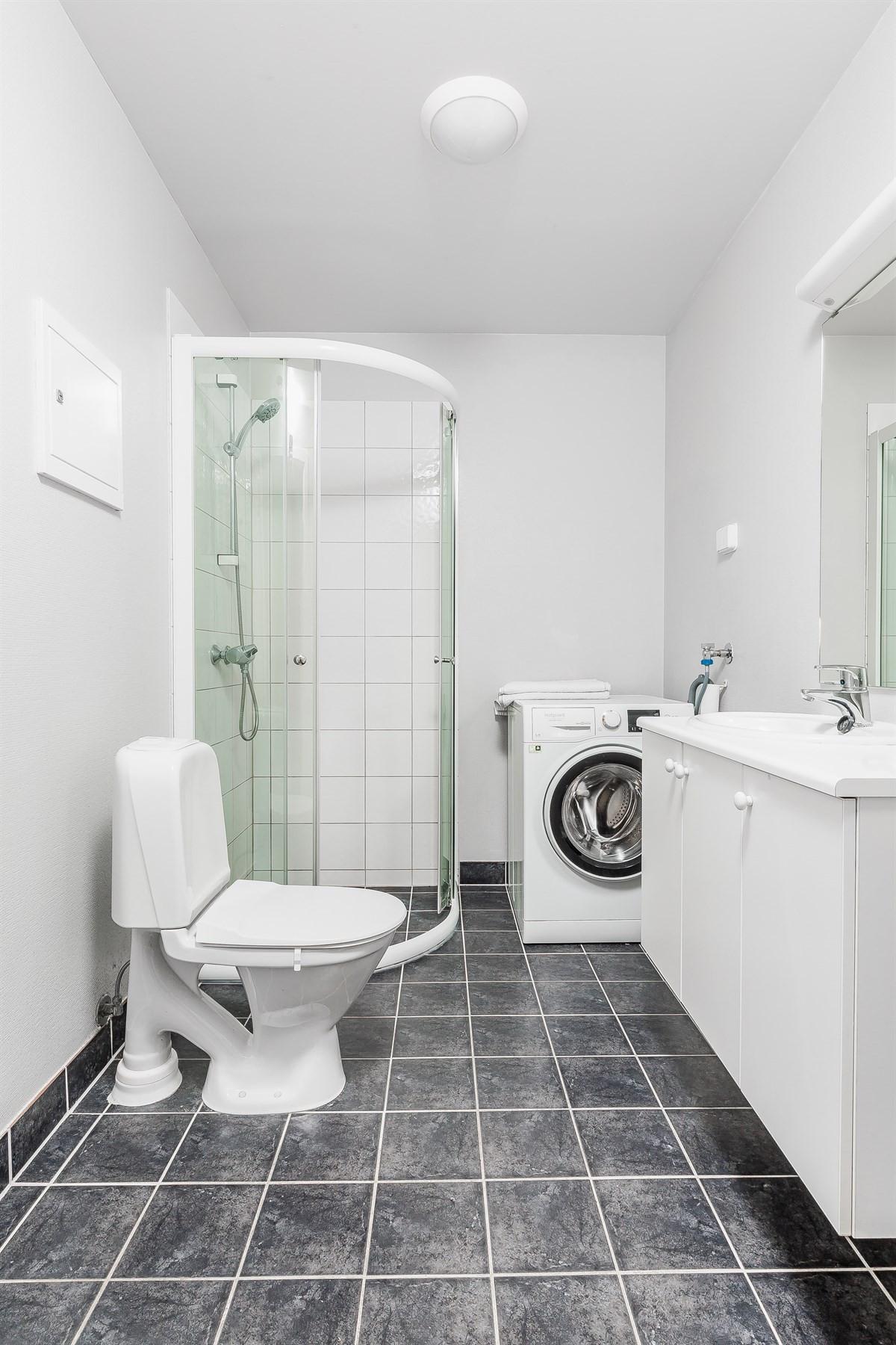 Flislagt baderom med gulvvarme, gulvstående klosett, dusjnisje og opplegg for vaskemaskin