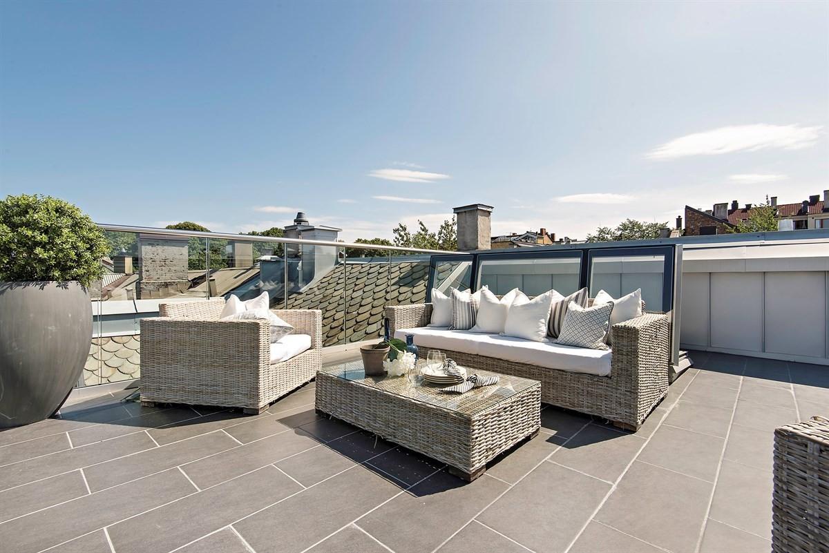 Terrassen måler ca. 36 kvm, noe som gir plass for møblering, og her er solforholdene tilnærmet optimale. Takterrassen har grå fliser på gulv med underliggende gulvvarme, og et rekkverk i stål og herdet glass