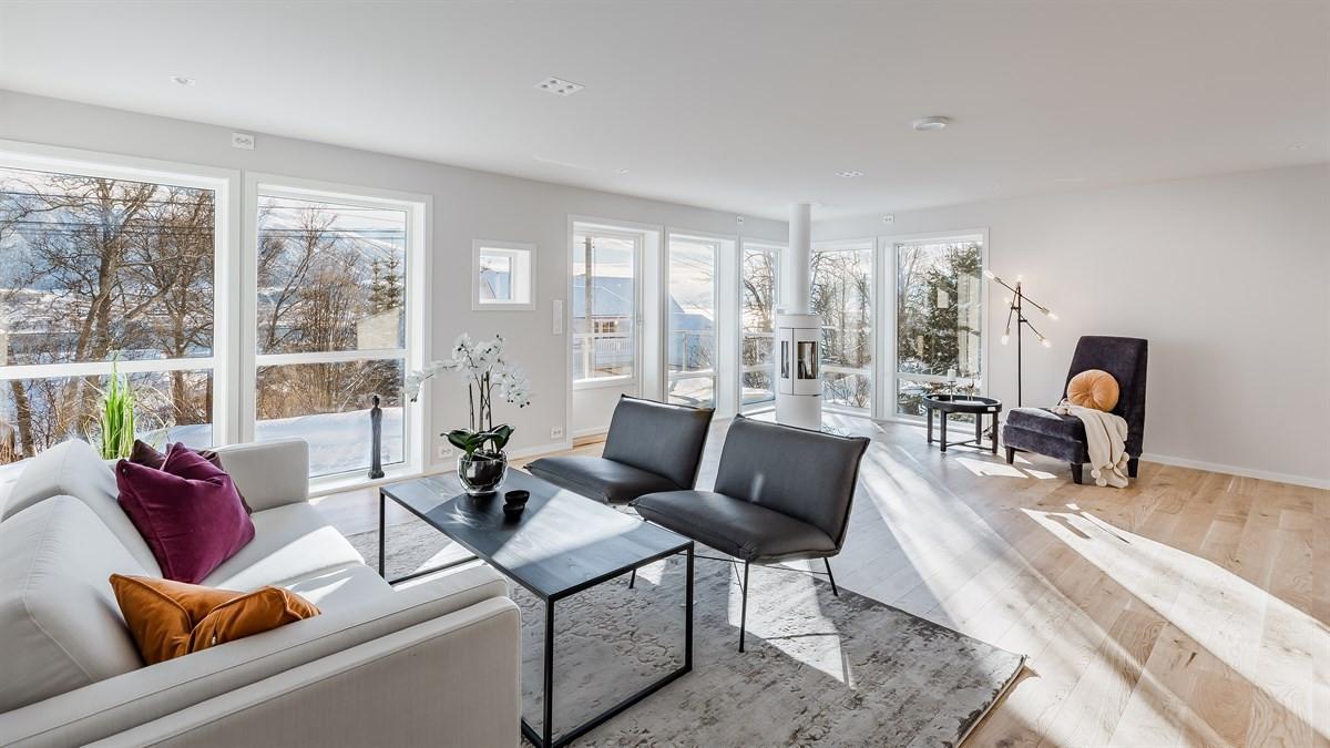 Lys og trivelig stue med store vindusflater som gir masse lysinnslipp.