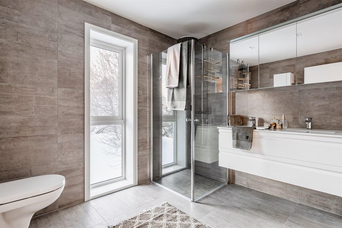 Flislagt bad med moderne innredning og vegghengt toalett.