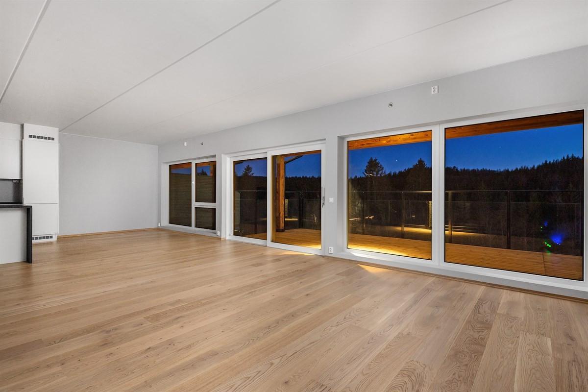 Stor, åpen stue- og kjøkkenløsning med store vindusflater
