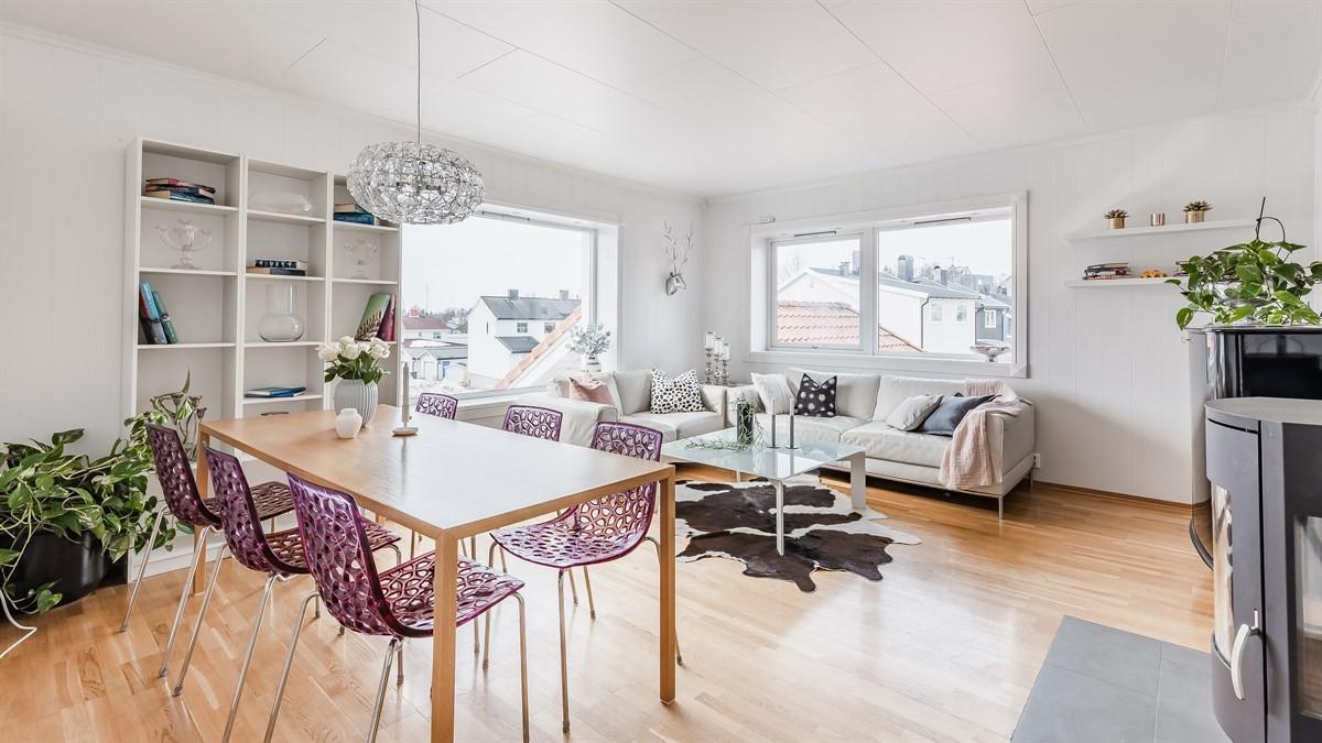 Romslig stue med god plass til salong og spisebord og vedfyring.