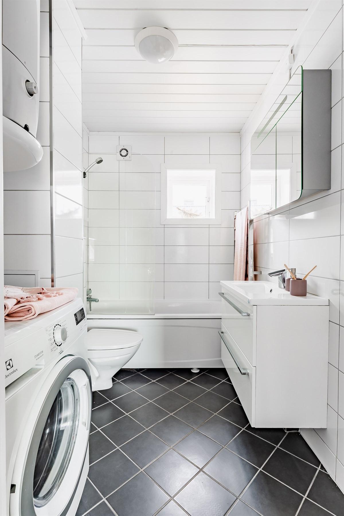 Bad med badekar og vegghengt toalett