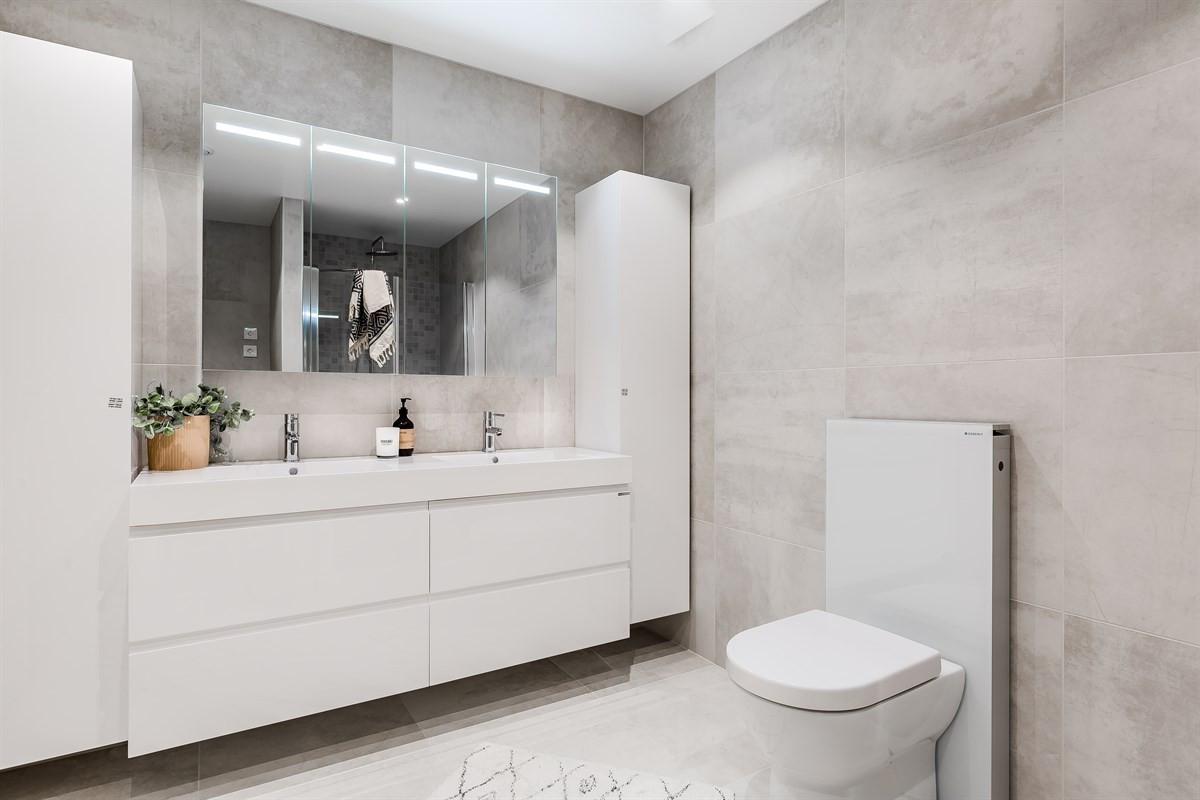 Komplett fliselagt baderom med toalett, dobbel servant og gode oppbevaringsmuligheter i moderne baderomsinnredning