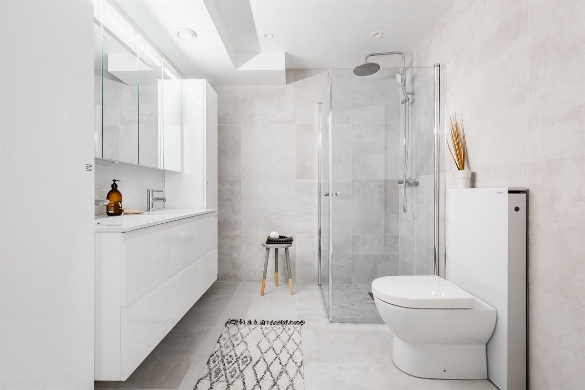 Komplett fliselagt baderom med toalett, dusjnisje og moderne baderomsinnredning