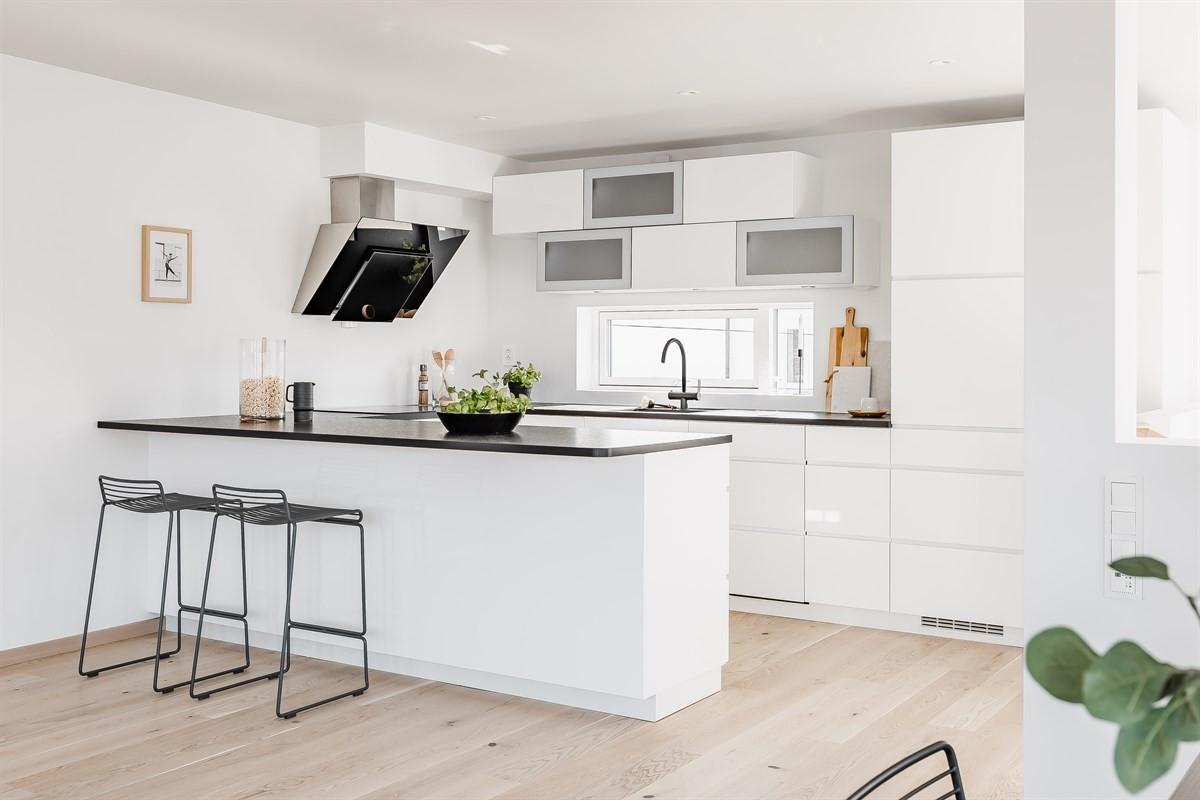 Moderne kjøkkeninnredning med lyse glatte fronter og integrerte hvitevarer