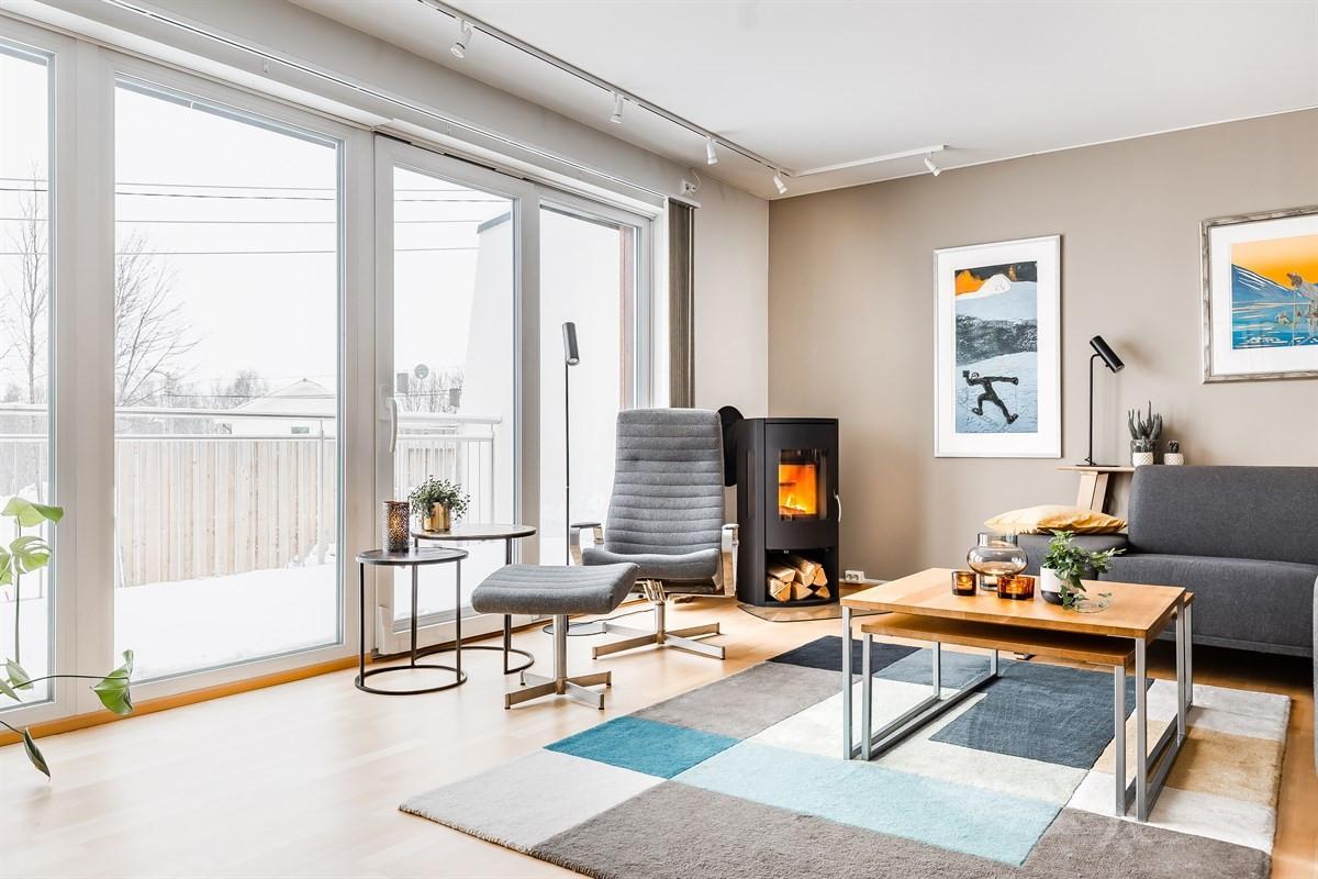 Lys og innbydende stue med store vindusflater og utgang til veranda