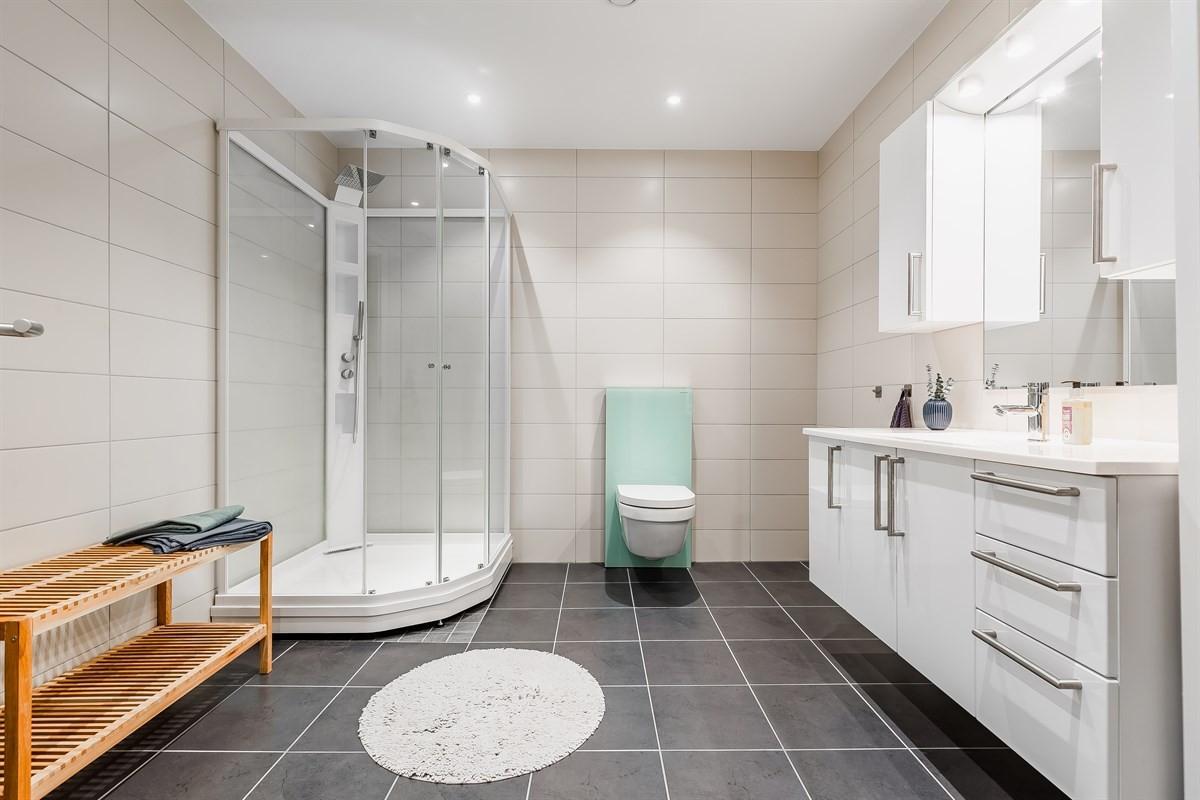 Hovedbad med fliser, spotter i tak, dusjkabinett og innredning