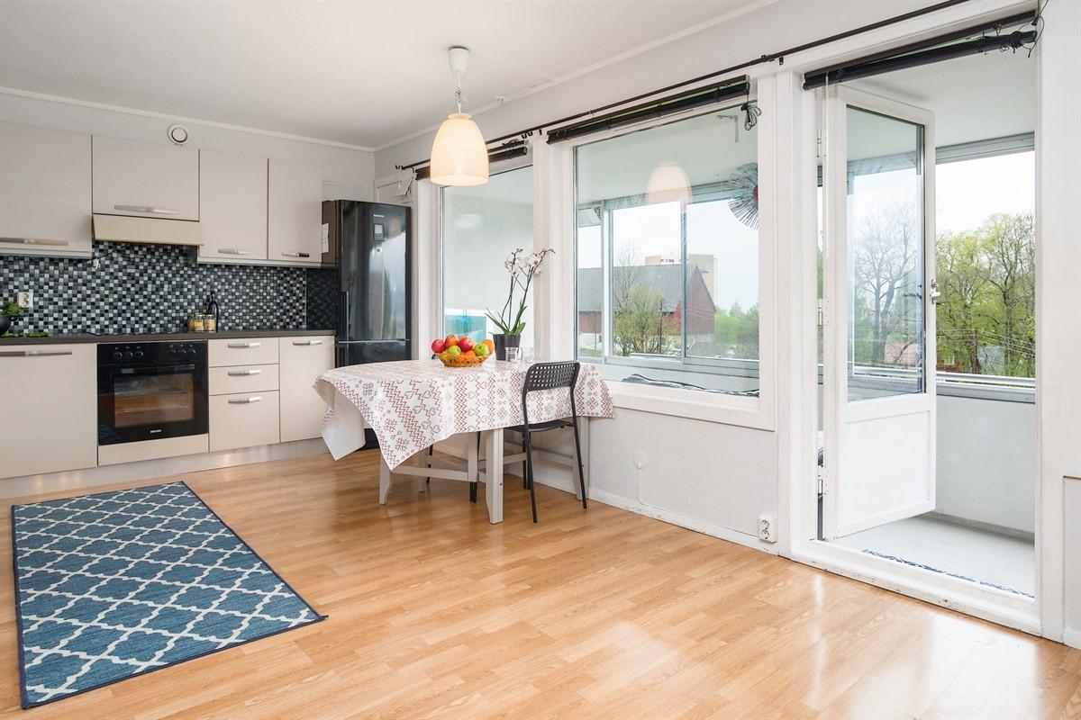 Hyggelig kjøkken med spiseplass i delvis åpen løsning mot stue