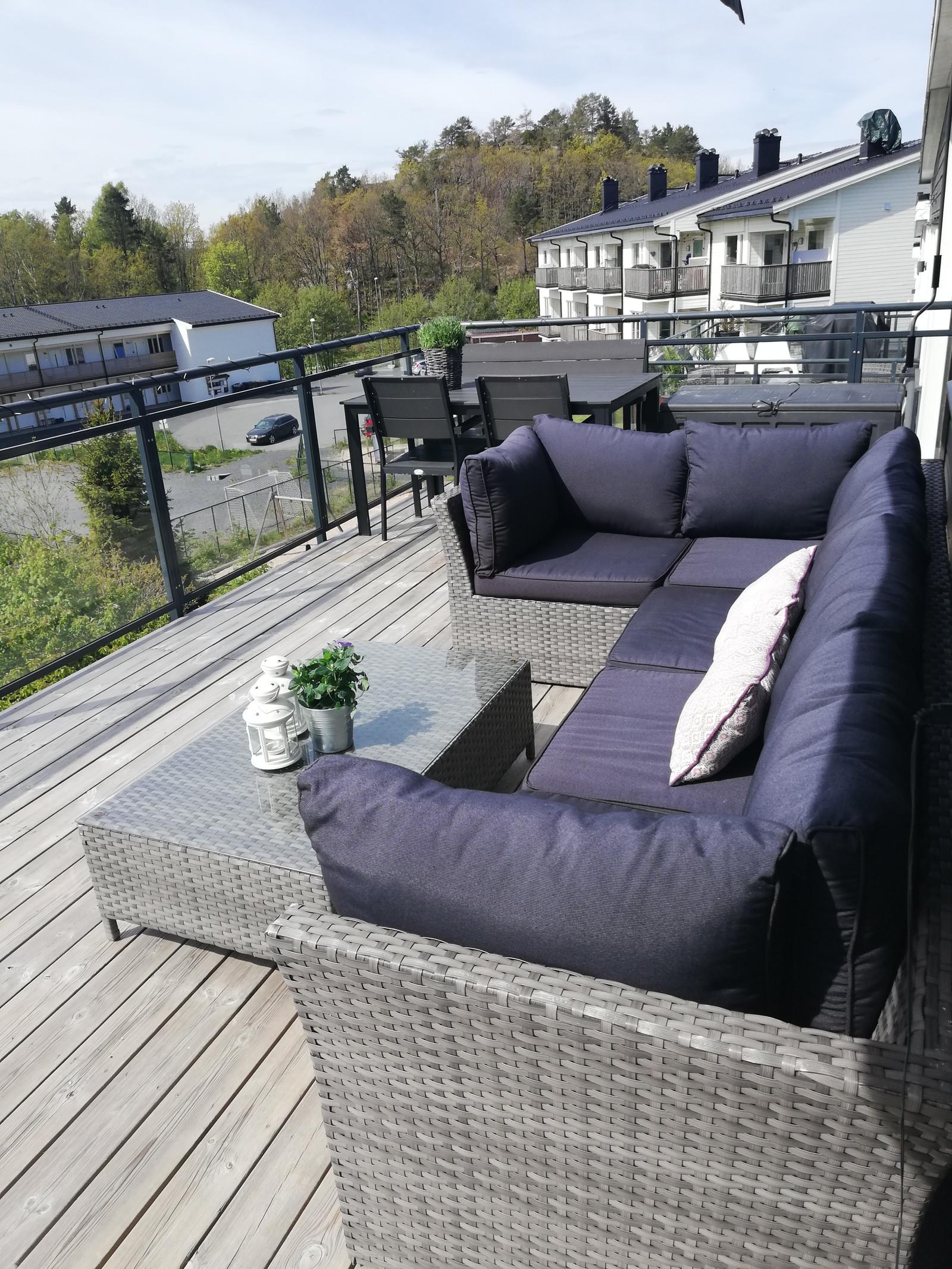 Stor, solrik veranda med hjørnespfa og spisebord.