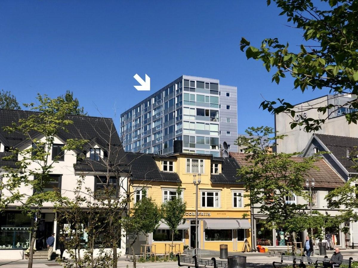 Stor toppleilighet med vedfyring og garasje i Sentrum Terrasse. Bildet er tatt fra kirkeparken i sentrum og viser leilighetens nærhet til gågata.
