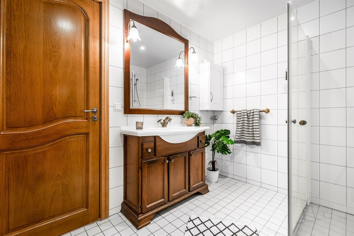 Fliselagt baderom med delikat innredning, dusjhjørne og vegghengt wc