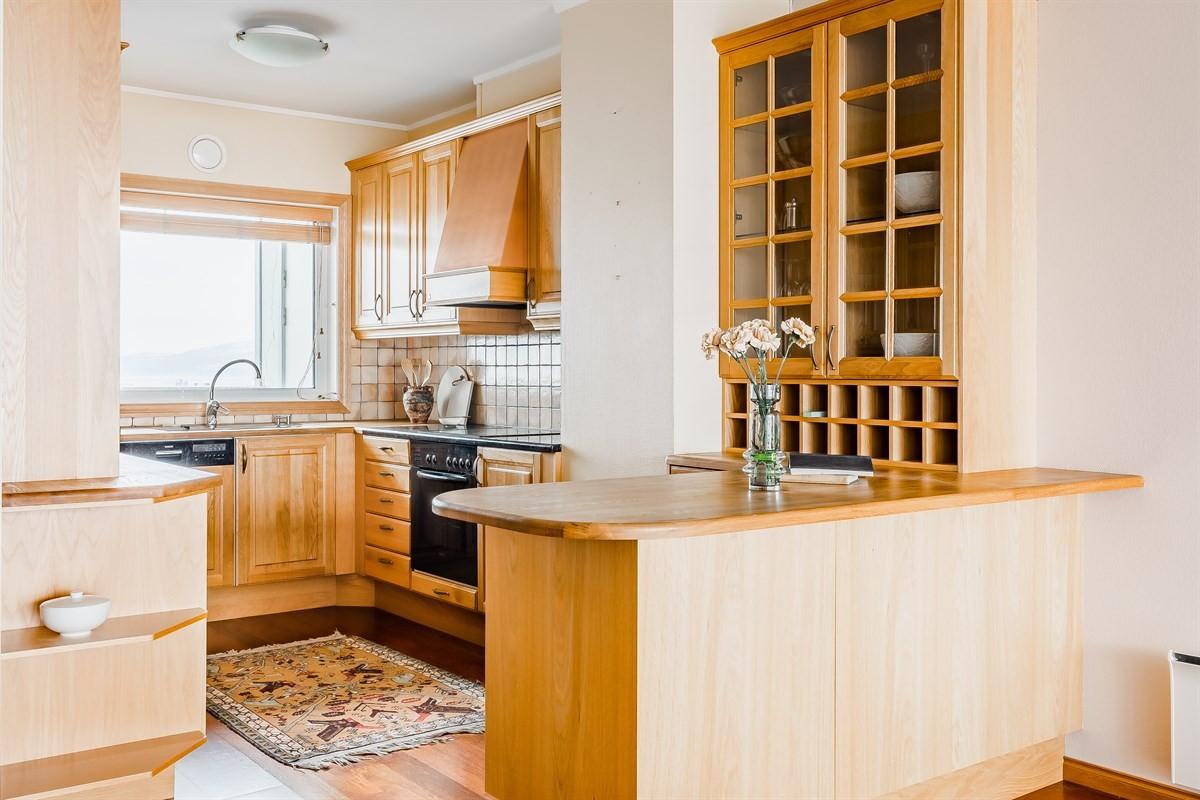 Pen kjøkkeninnredning med integrerte hvitevarer og praktisk barløsning mot stue