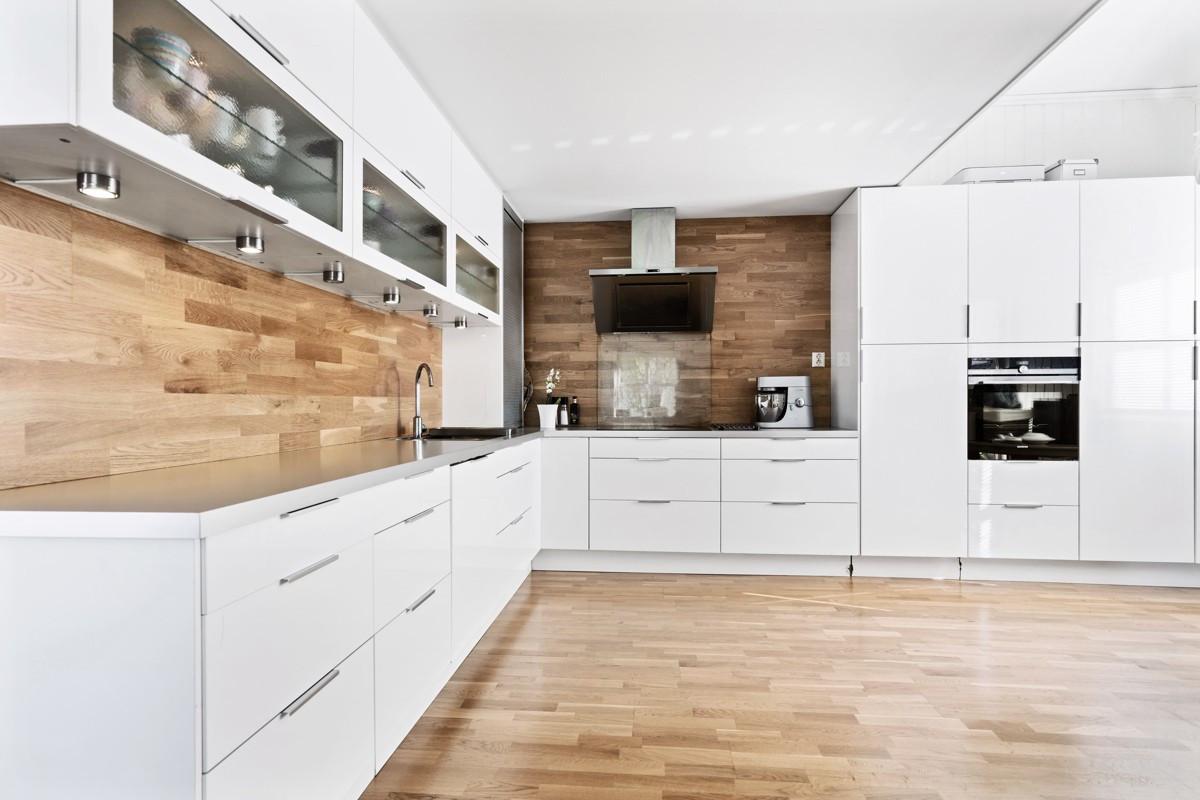 Moderne kjøkken med glatte fronter og integrert stekeovn, oppvaskmaskin, kjøl og fryseskap