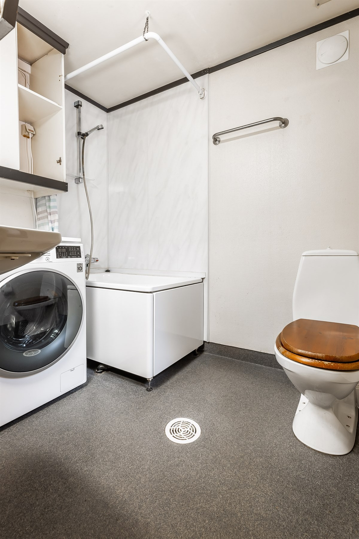 Baderom tilhørende leilighet i første etasje. Opplegg for vaskemaskin, dusj med badekar. Ventilasjon i himling.