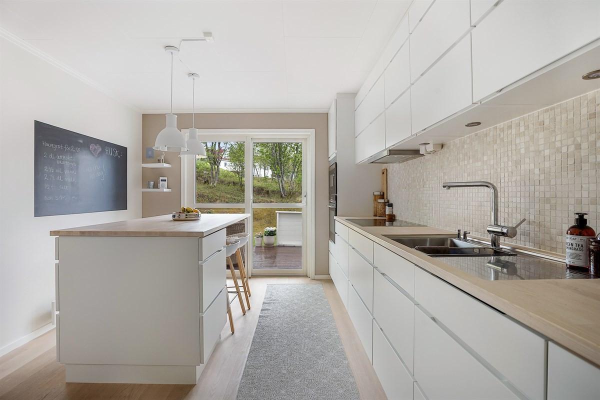 Kjøkkenet er tidløst og svært romslig med takhøye skap