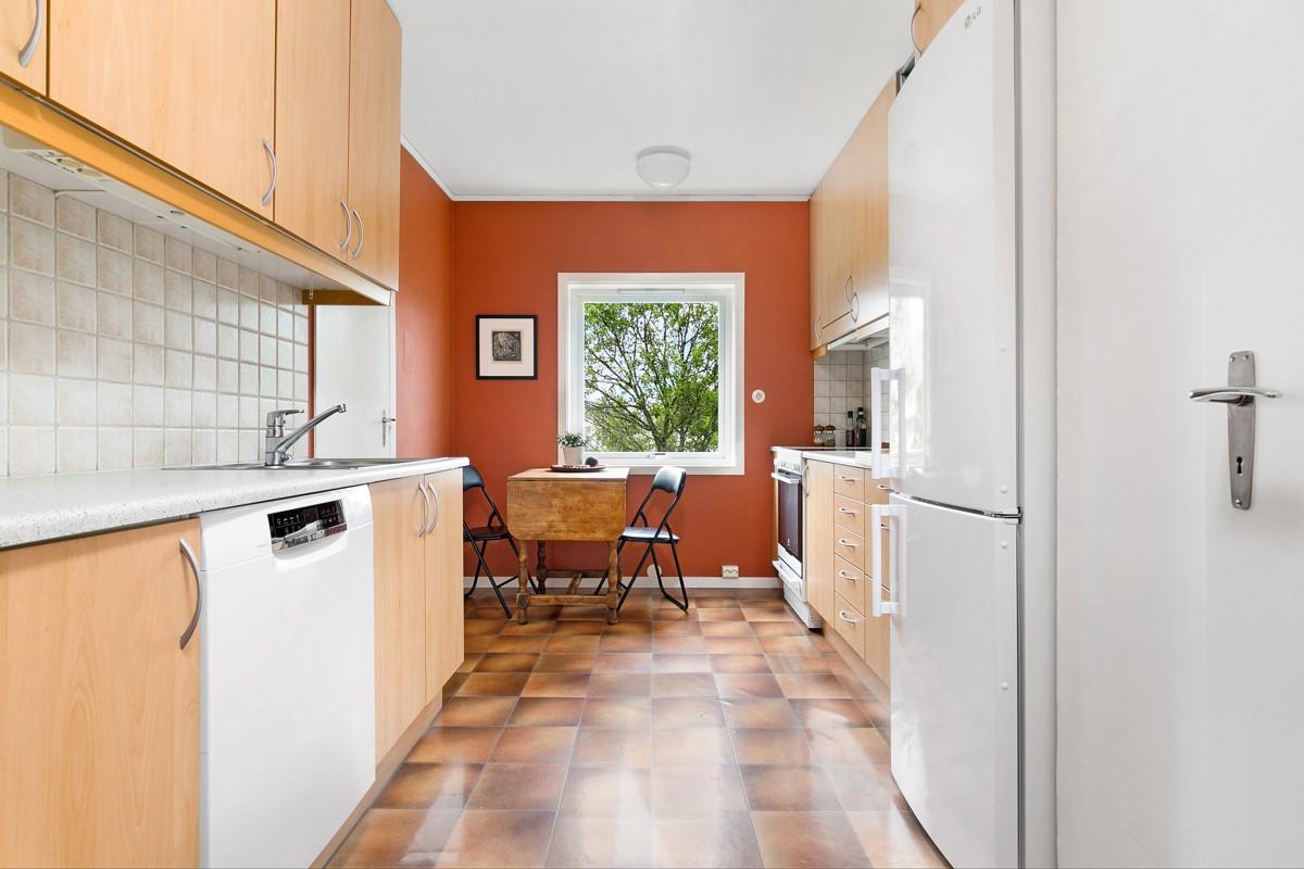Kjøkken med med takhøye skap og spiseplass