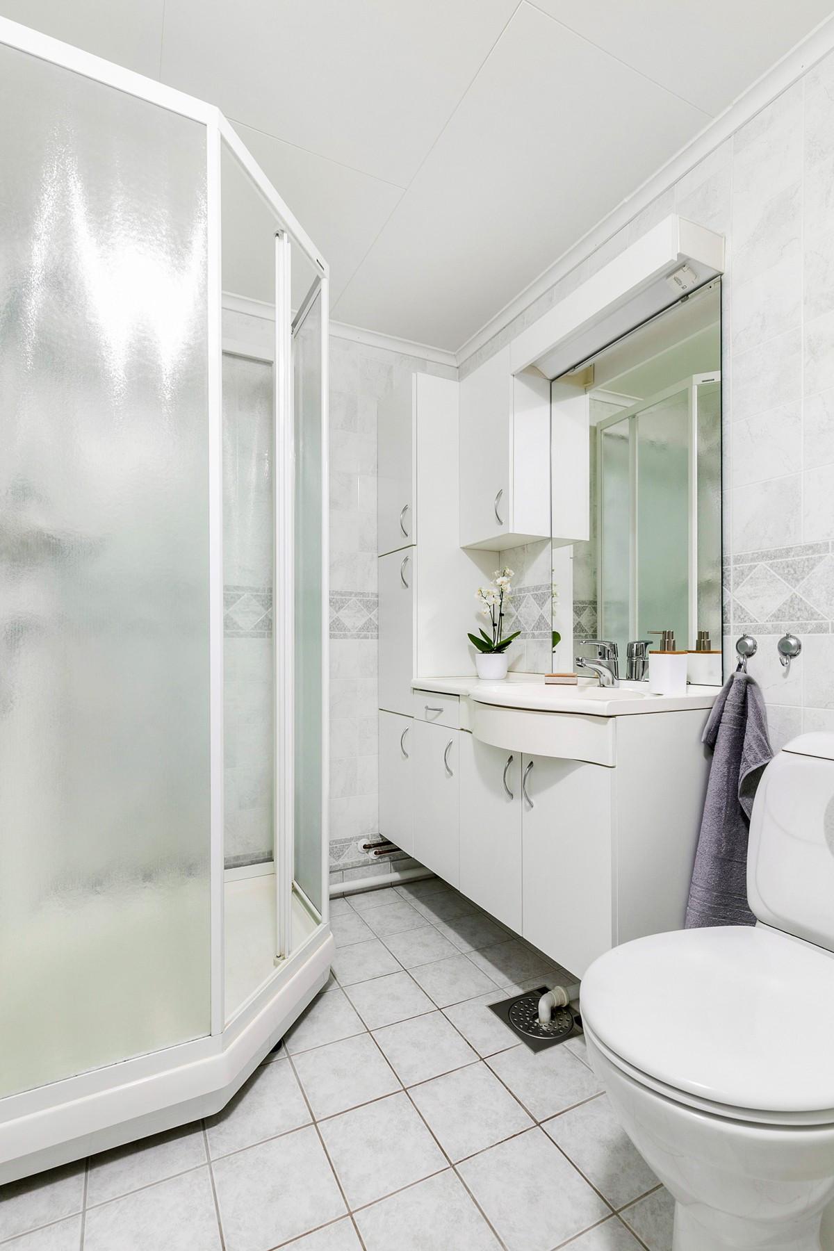 Bad med fliser på gulv og våtromspanel på vegger - varmekabler