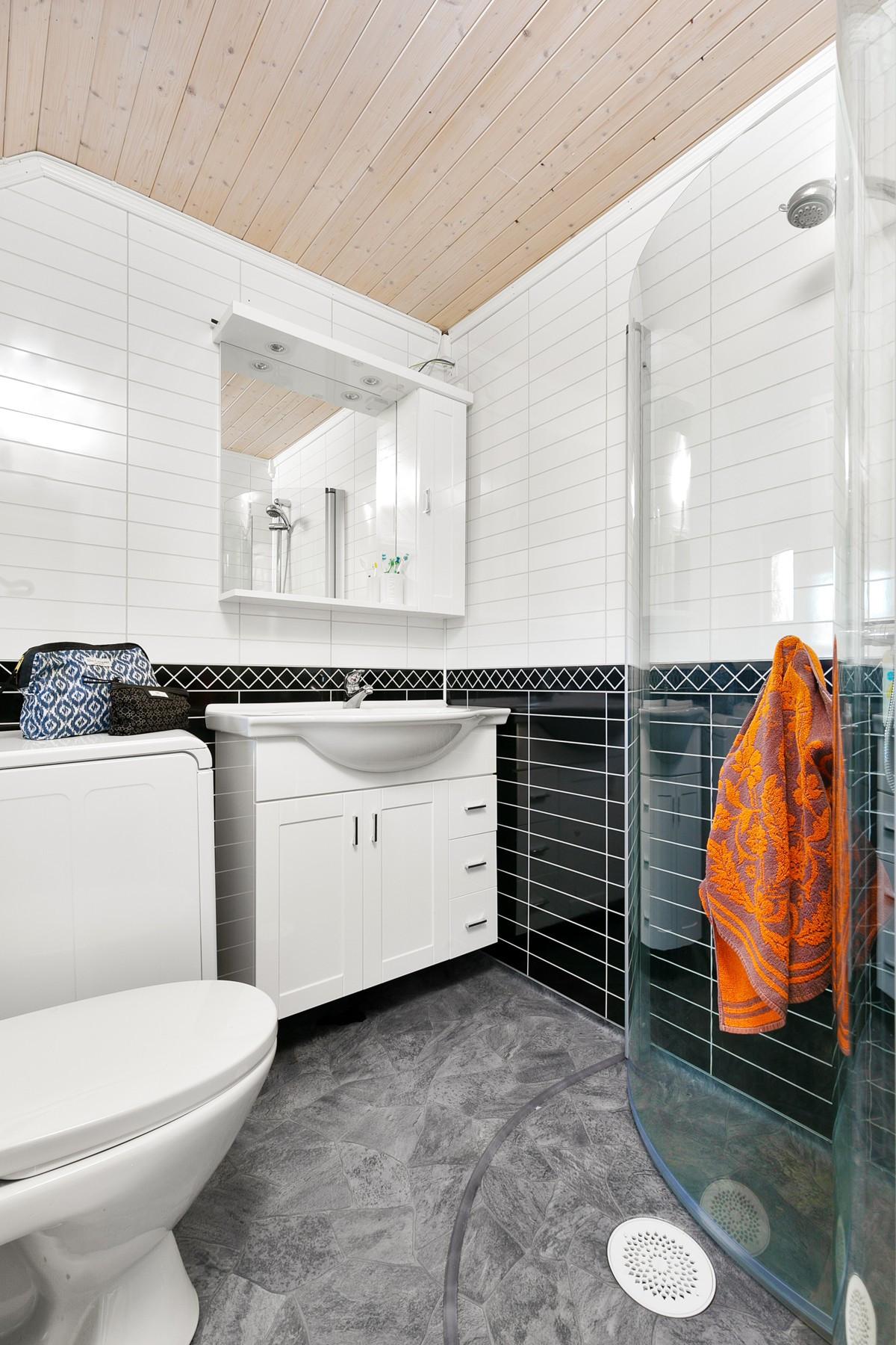 Bad/vaskerom er innredet med dusj på vegg med innsvingbare dører, servant med skap, wc og opplegg for vaskemaskin