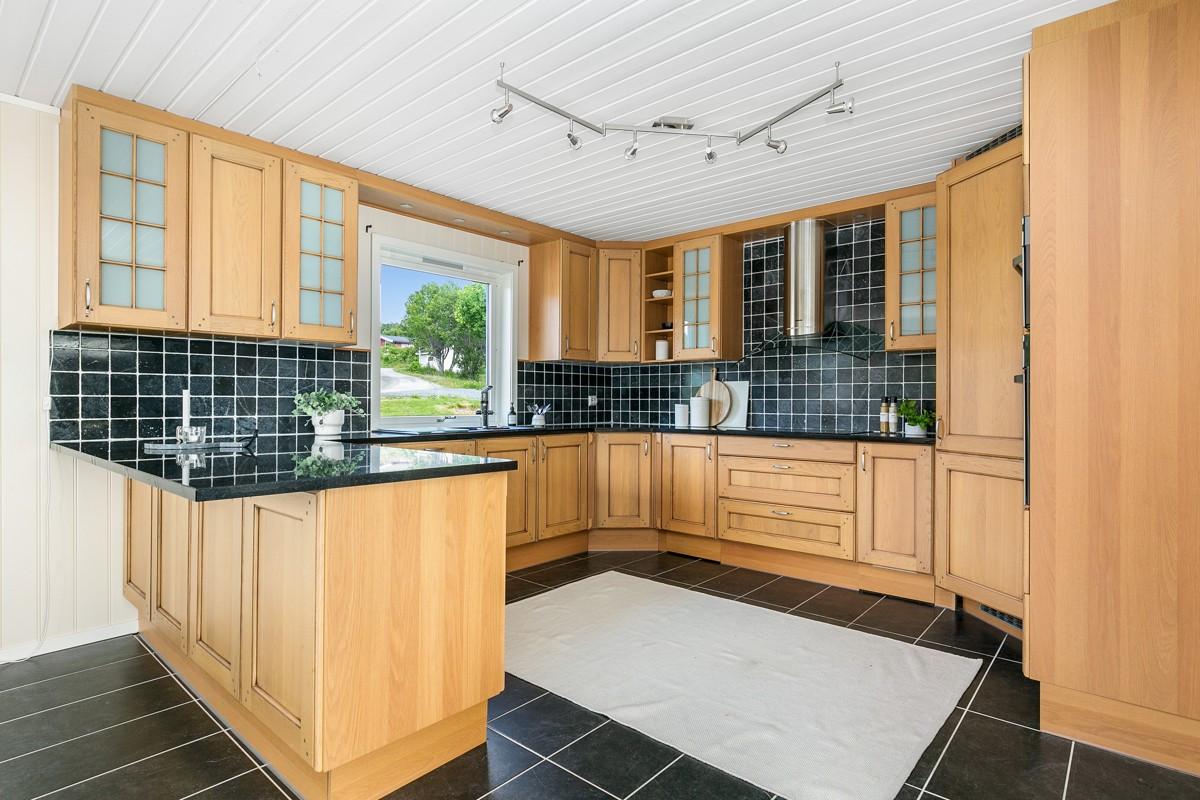 Pent kjøkken med barløsning og rikelig med oppbevaringssplass, samt integrerte hvitevarer