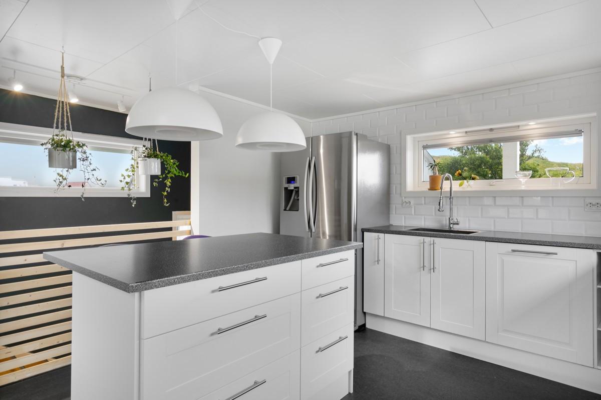 Kjøkkeninnredning fremstår moderne med hvite lakkerte fronter og benkeplate i laminat