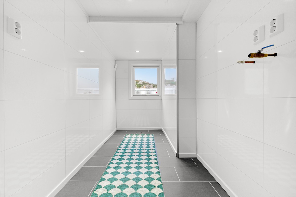 Fliselagt gulv på vaskerom med gulvvarme og opplegg for vaskemaskin