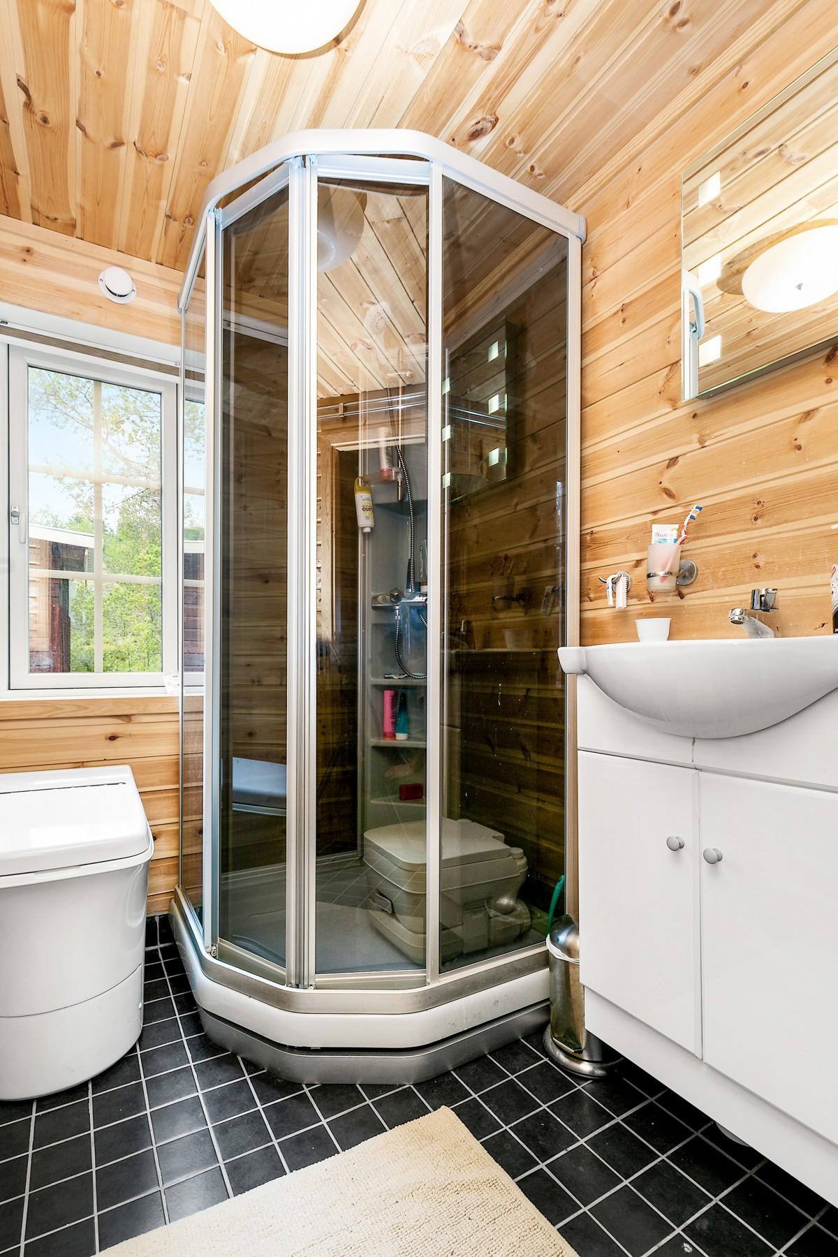 Bad er innredet med dusjkabinett, Cinderella forbrenningstoalett, samt gulv er fliselagt med varmekabler