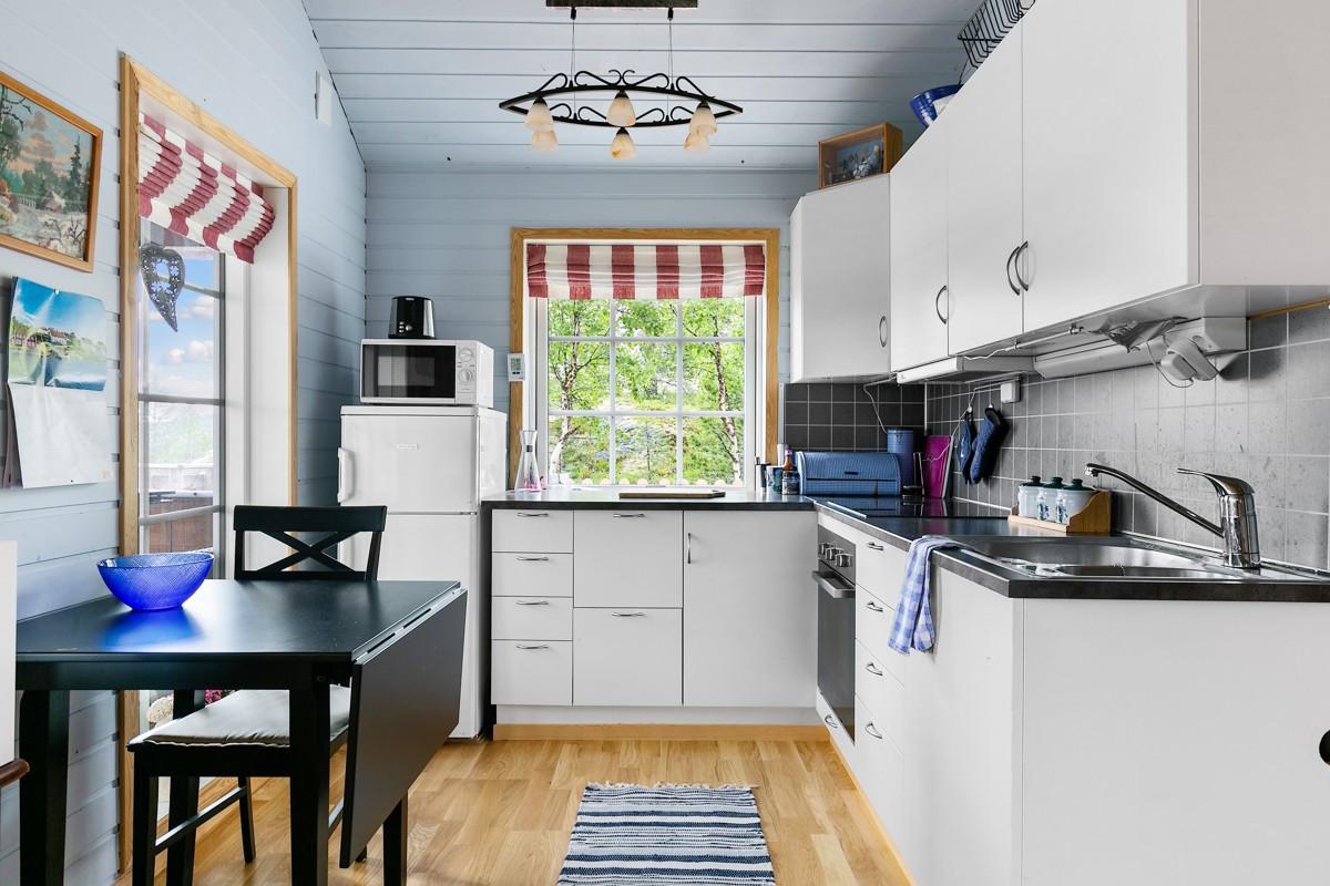 Kjøkken er innredet med integrert koketopp og stekeovn, samt god skap- skuffeplass til oppbevaring