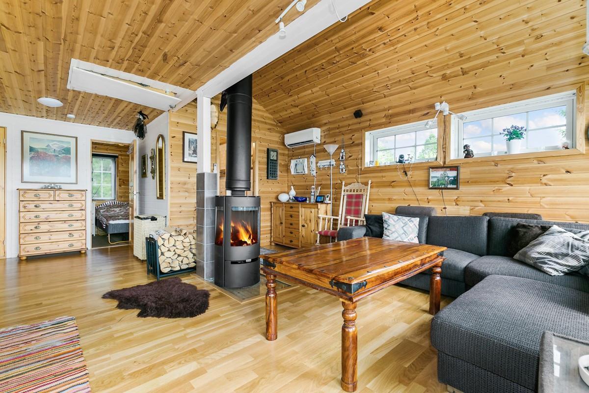 Vegger med trepanel bidrar til den koselige hytte-følelsen. Vedovn montert i stue gir god varme på kalde vinterdager
