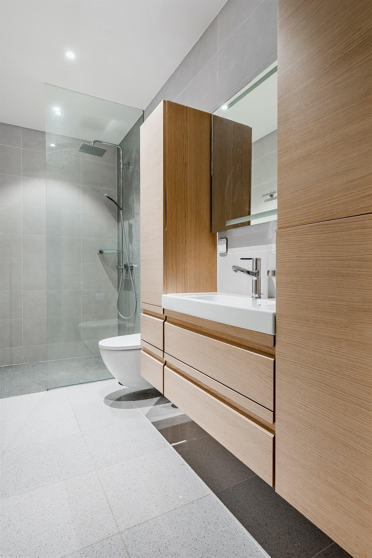 Baderom med dusjhjørne, wc, servant og godt med skapplass