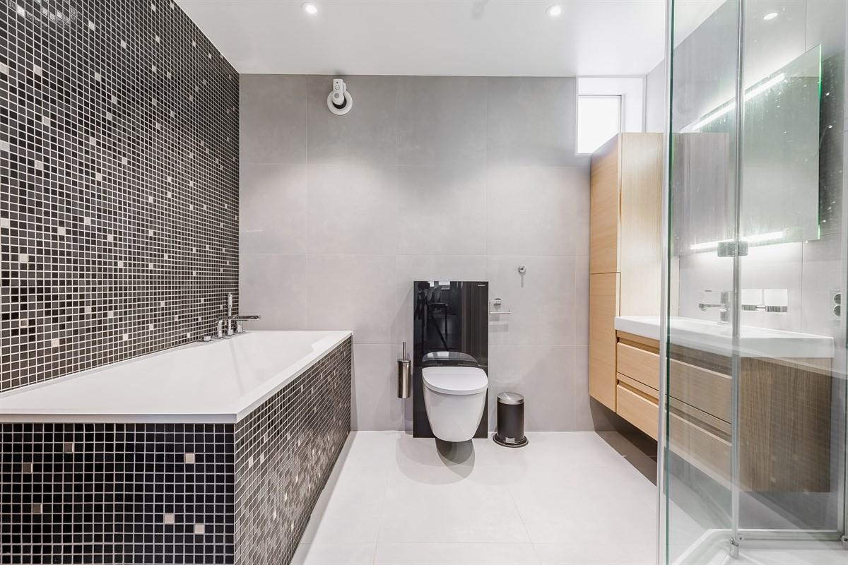Flislagt bad og badekar - i taket er det montert dowlights