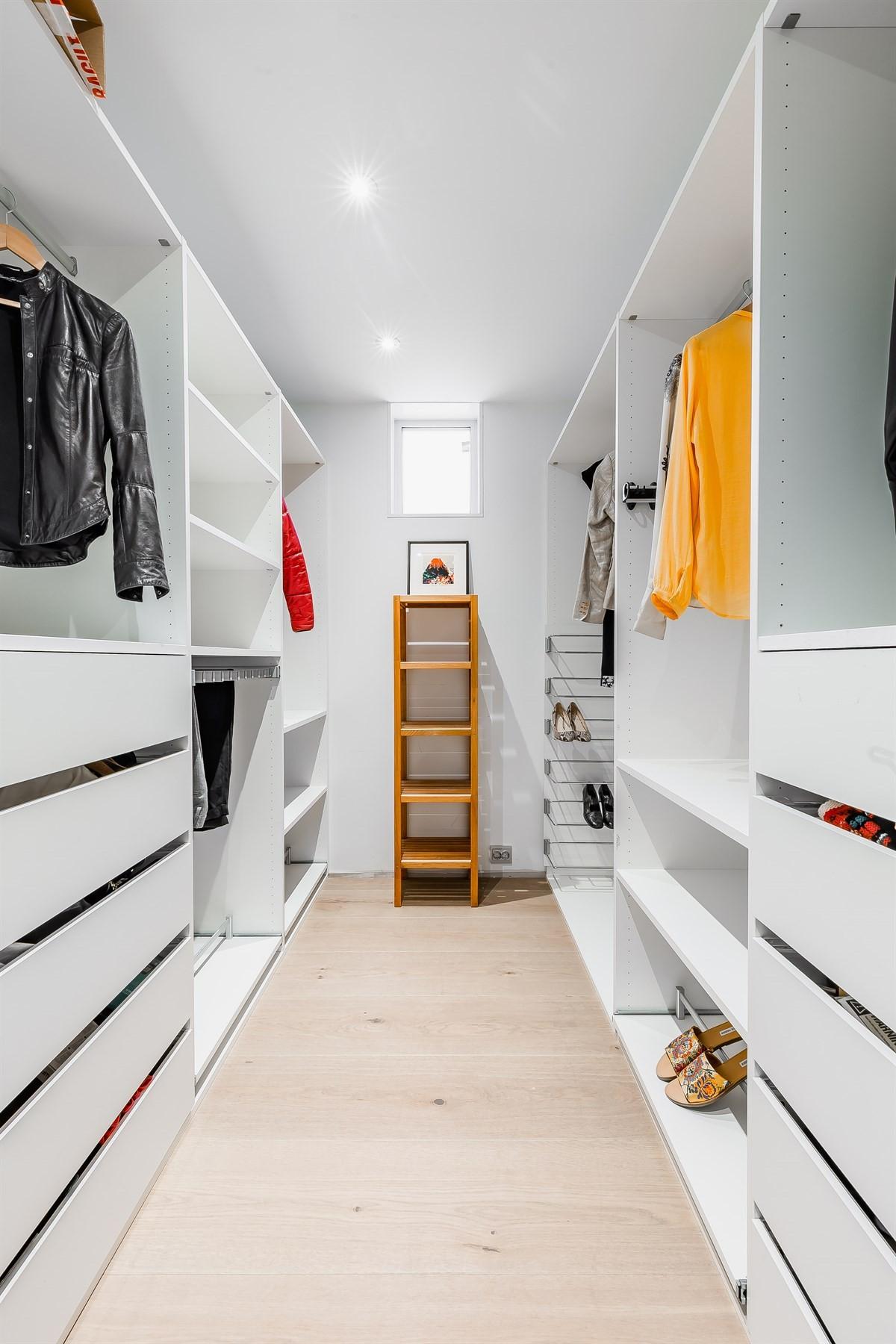 Stor walk-in garderobe med monterte dowlights i taket