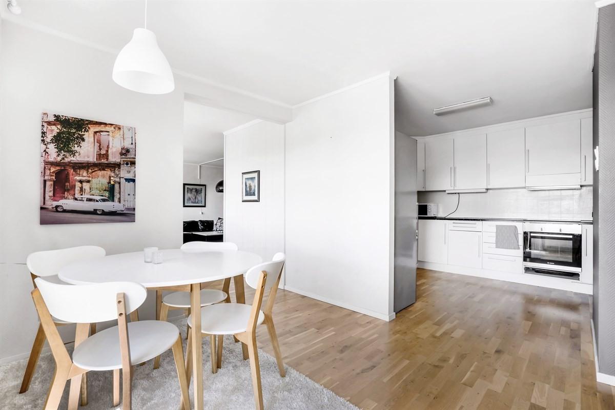 Kjøkken med hvite, glatte fronter og god plass til spisebord ved vinduene