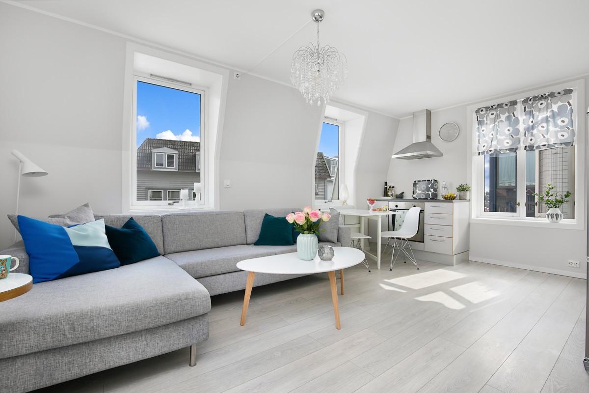 Lys og trivelig stue/kjøkken-løsning med flere vinduer som gir gjennomgående lysinnslipp