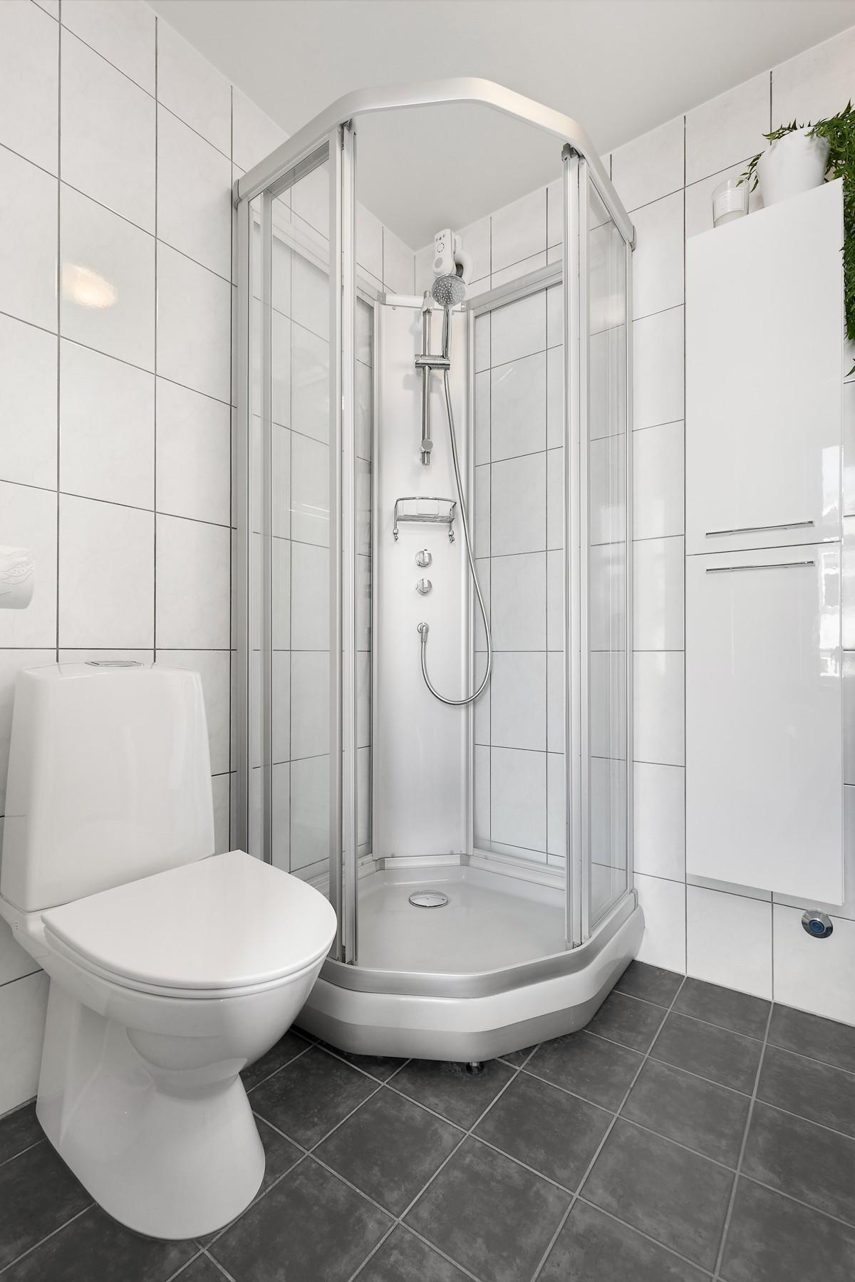 Fliselagt bad med dusjkabinett, wc, vegghengt skap, servant med skuffer, speilskap og vaskemaskin