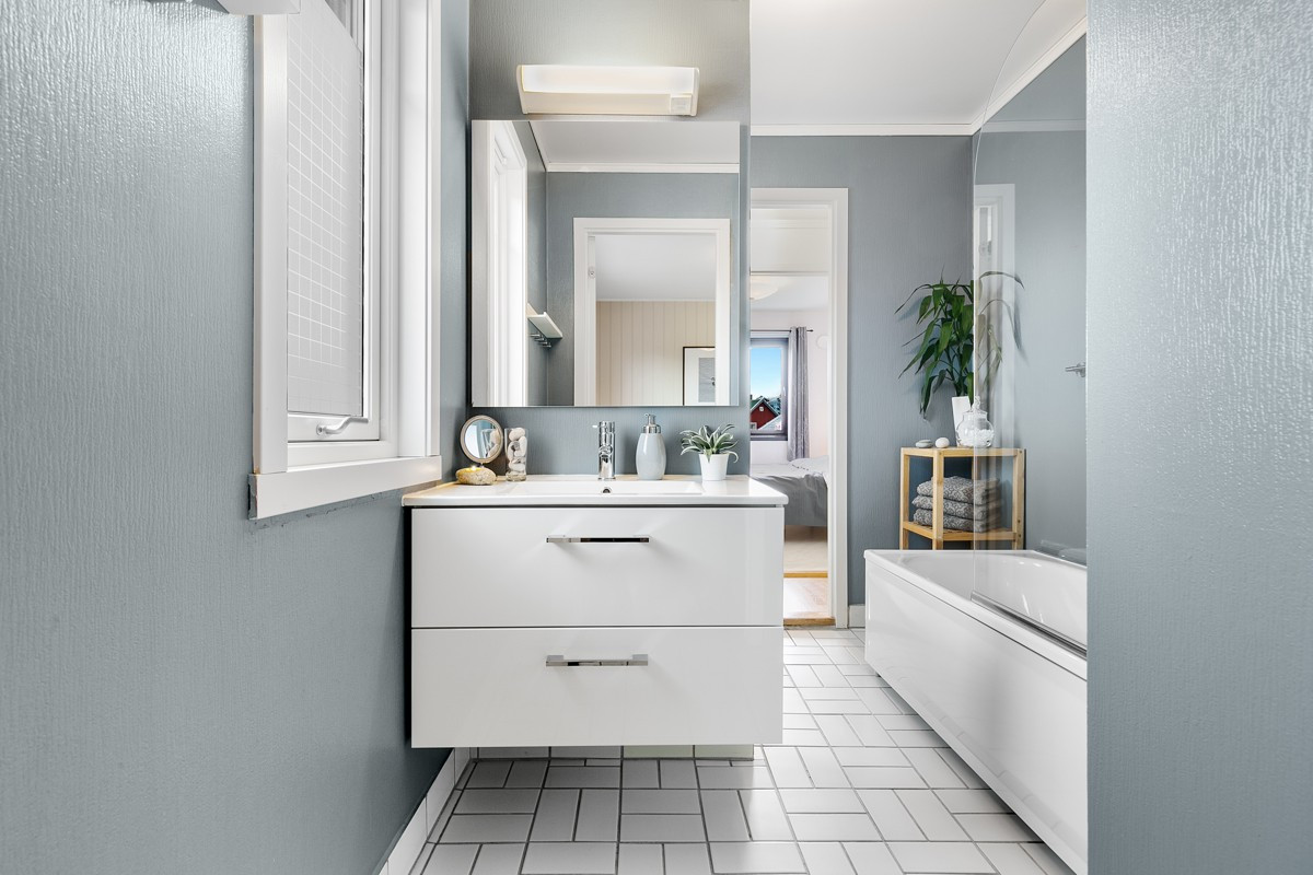 Baderom med mye naturlig lys, flislagt gulv med varmekabler og moderne fargevalg
