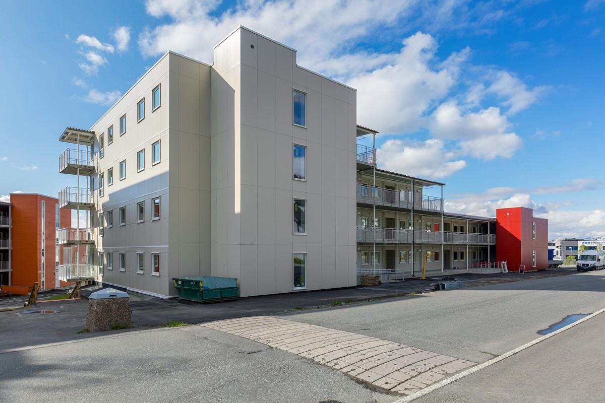 Fasade sett fra baksiden av leilighetskomplekset. Kort vei til dagligvarebutikk og bussholdeplass