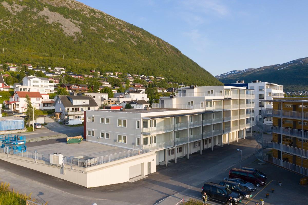 Fasade sett fra forsiden, med innkjøring til garasjeanlegg og parkeringsplasser