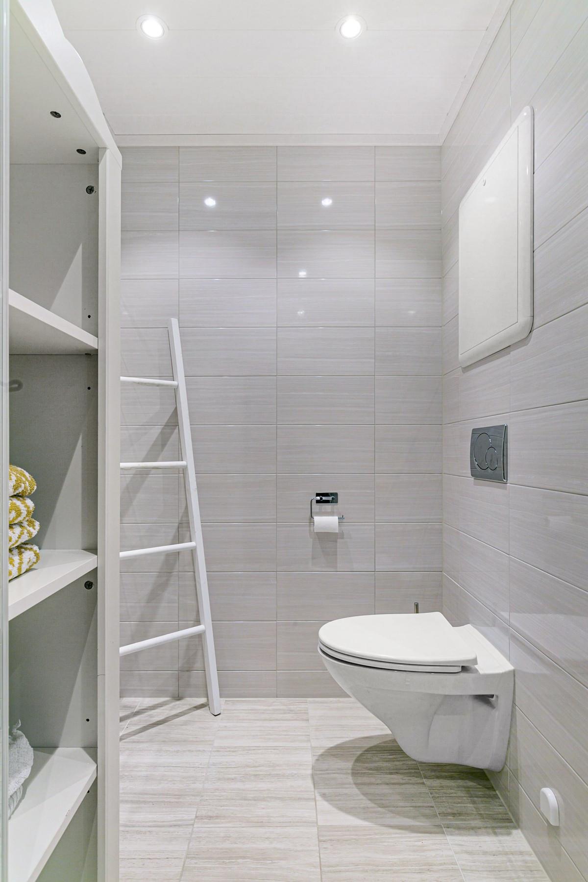 Badet består av dusjhjørne, wc og dobbelservant med speil over