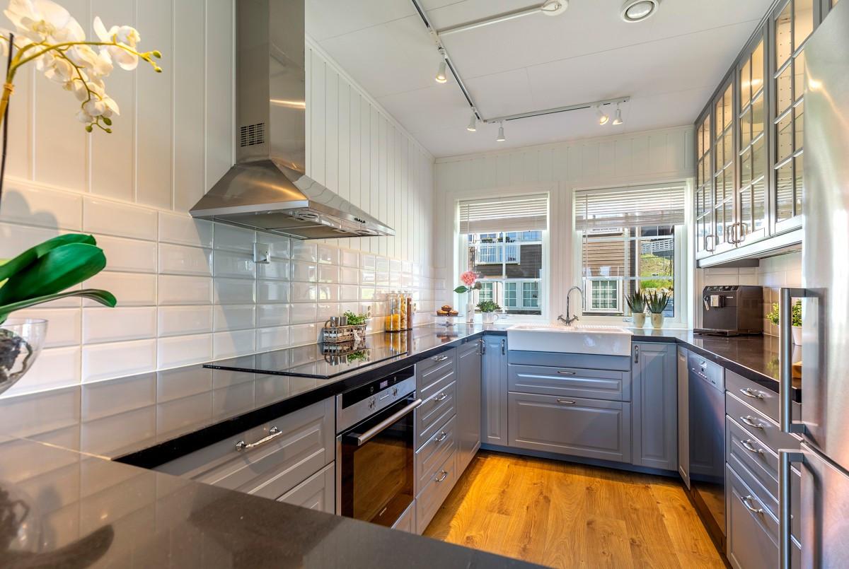 Lekkert kjøkken med sort stein benkeplate, vitrineskap med lys, integrerte hvitevarer mm.