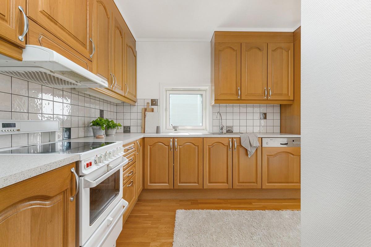 Pent kjøkken med fliser over benk, eikefronter og integrert oppvaskmaskin, samt kjøl/frys