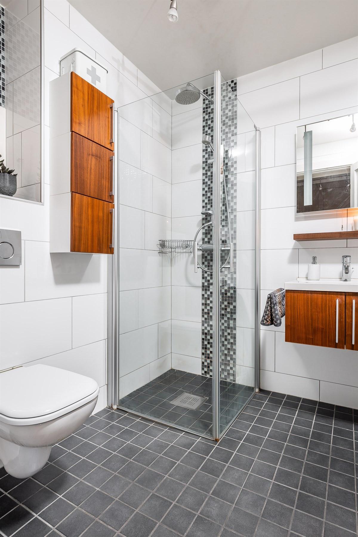Komplett fliselagt baderom med varme i gulv og rikelig med skapplass