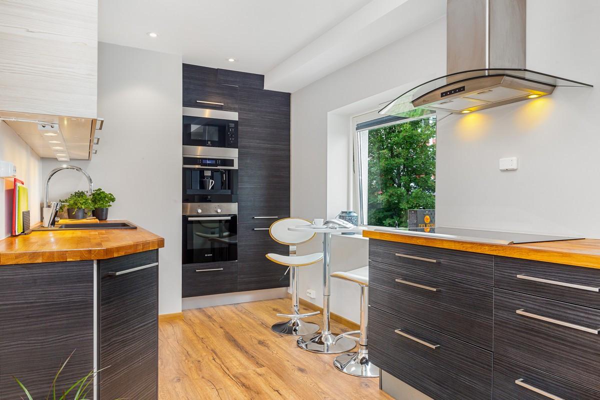 Kjøkkenet er moderne innredet med heltre benkeplate og integrert stekeovn, kjøl/frys, mikro, oppvaskmaskin, kaffemaskin og brei induksjonstopp