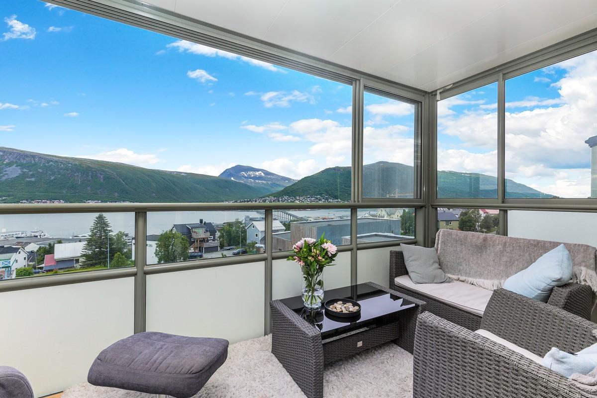 Stor innglassert balkong med fantastisk utsikt mot Tromsøysundet og Tromsdalstinden