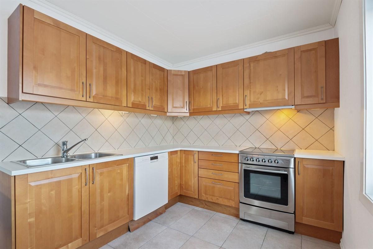 Kjøkkeninnredning med profilerte fronter og flislagt over laminat benkeplate.